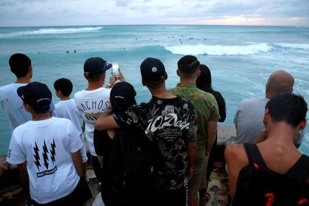 Tourists watch surfers in Waikiki Bay as Tropical Storm Lane approaches Honolulu, Hawaii, U.S. August 24, 2018. REUTERS/Terray Sylvester