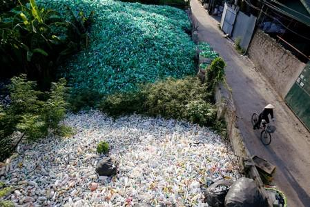 FILE PHOTO: Vietnamese woman cycles past recyclable plastic bottles at Xa Cau village