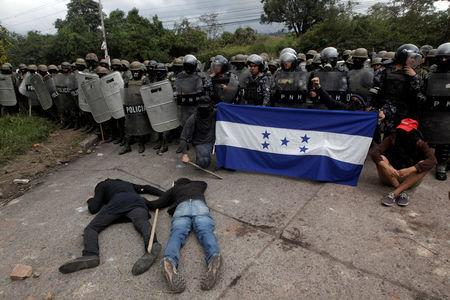 Opposition supporters hold a Honduran flag as others lie on the floor in front of security forces during a protest over a contested presidential election with allegations of electoral fraud in Tegucigalpa, Honduras, December 22, 2017. REUTERS/Jorge Cabrera