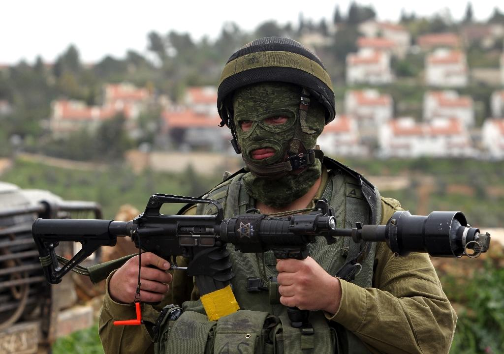 An Israeli soldier holds his weapon during clashes with Palestinian protesters on March 28, 2015, in the West Bank village of Nabi Saleh