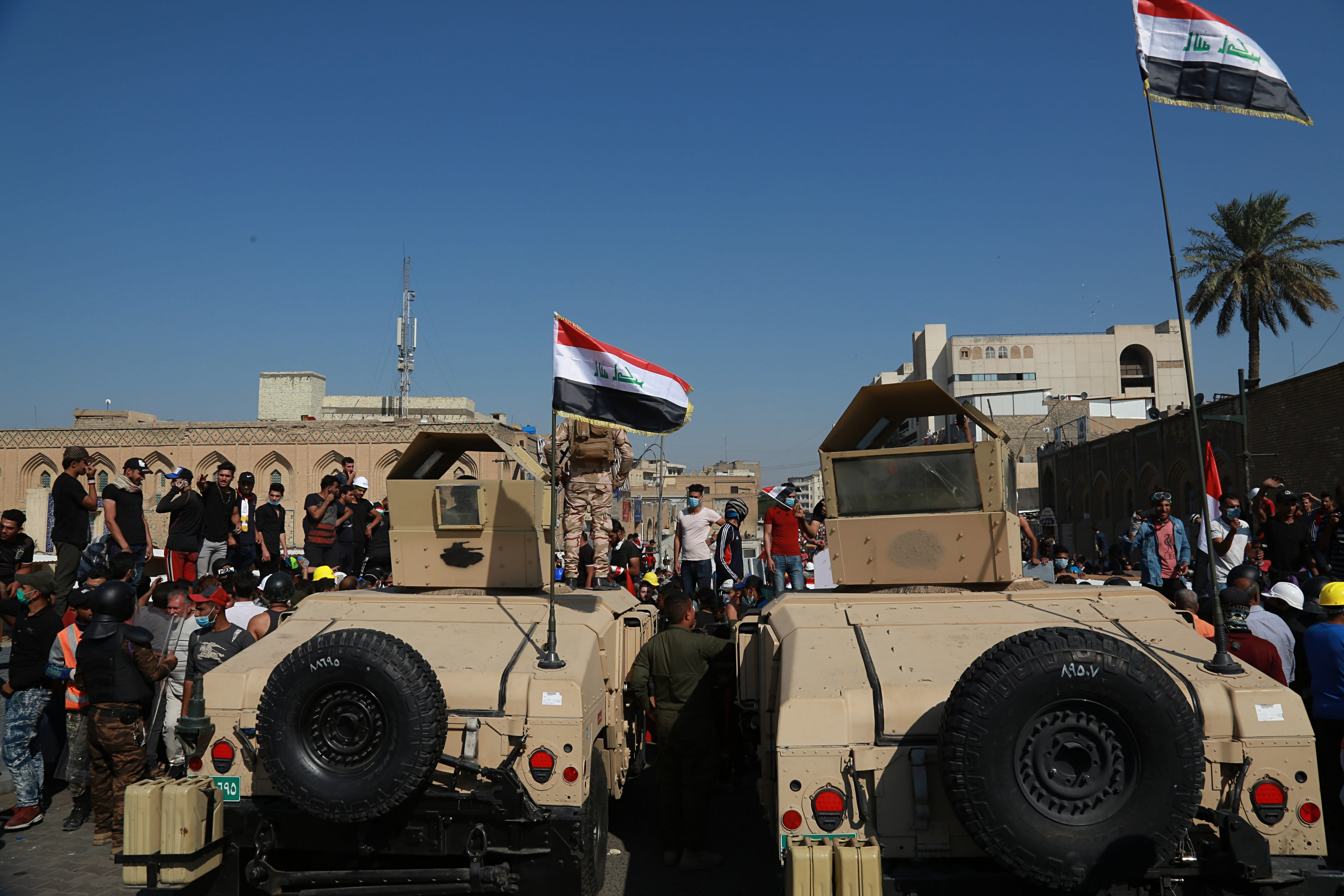 Army soldiers try to prevent anti-government protesters from crossing the al- Shuhada (Martyrs) bridge in central Baghdad, Iraq, Wednesday, Nov. 6, 2019. (AP Photo/Khalid Mohammed)