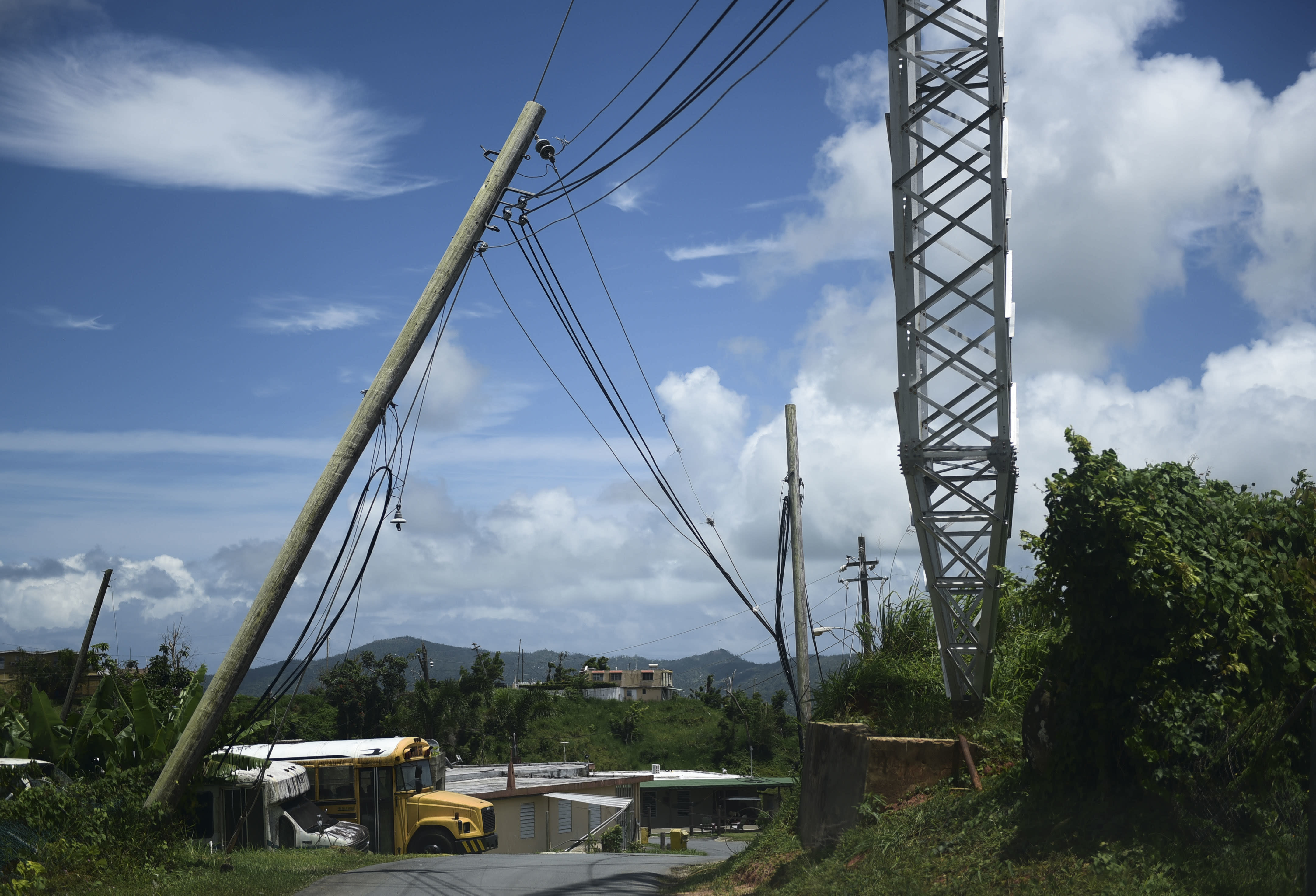 file - In this May 16, 2018 file photo, an electric power pole leans over the road in the Piedra Blanca area of Yabucoa, Puerto Rico, a town still mostly without power since it was struck by Hurricane Maria on Sept. 20. Puerto Rico's new governor announced on Sunday, Aug. 11, 2019 that she is suspending an upcoming $450,000 contract to rebuild and strengthen the island's power grid destroyed by Hurricane Maria. (AP Photo/Carlos Giusti, File)