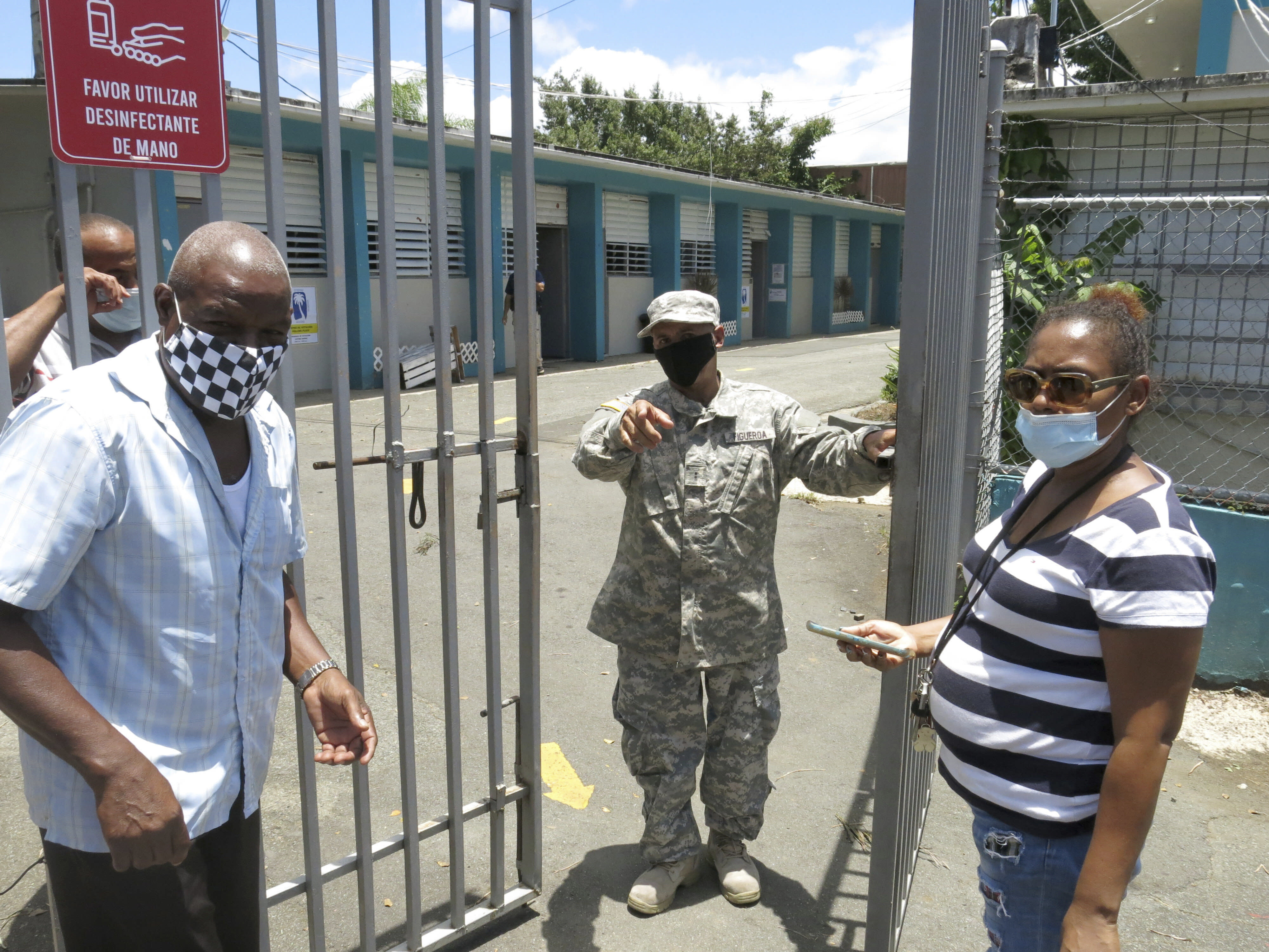 An official turns away two voters at a voting center lacking ballots in Carolina, Puerto Rico, Sunday, Aug. 9, 2020. Puerto Rico's primaries were marred on Sunday by a lack of ballots in a majority of centers across the U.S. territory, forcing frustrated voters who braved a spike in COVID-19 cases to turn around and go back home. (AP Photo/Danica Coto)