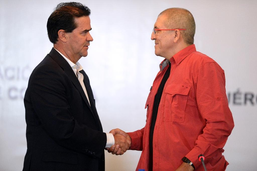 Head negotiators from the Colombian government and the left-wing ELN, Frank Pearl (L) and Antonio Garcia respectively, shake hands as they begin peace talks at the Foreign Ministry in Caracas on March 30, 2016 (AFP Photo/Federico Parra)