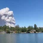 Thousands evacuate fast-moving California wildfire; homes burn