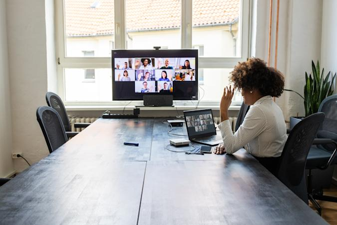 Rear view of a businesswoman having a meeting with team over a video conference in office board room. Meeting over a video call in office post pandemic lockdown.