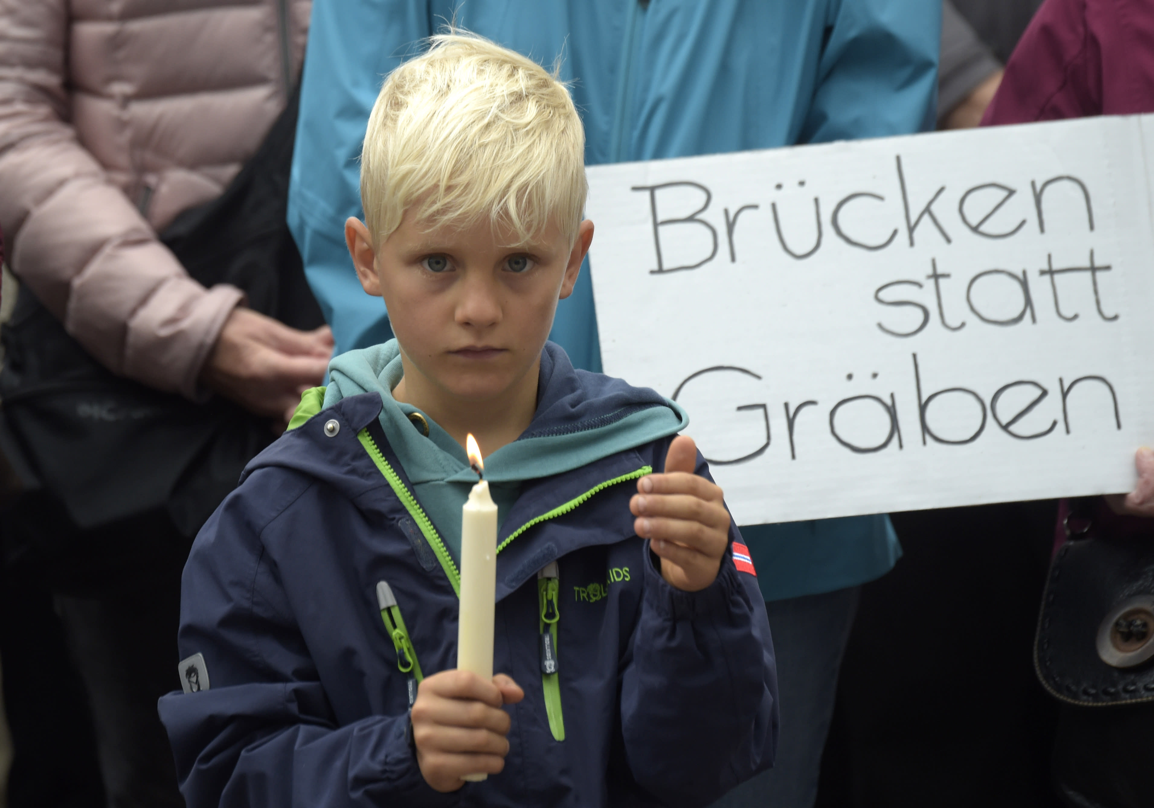 <p>A boy holds candles as he stands in front of a poster reading 'bridges instead of cleavages' during a demonstration for democracy and against extremism in Chemnitz, eastern Germany, Sunday, Sept. 2, 2018. (Photo: Jens Meyer/AP) </p>