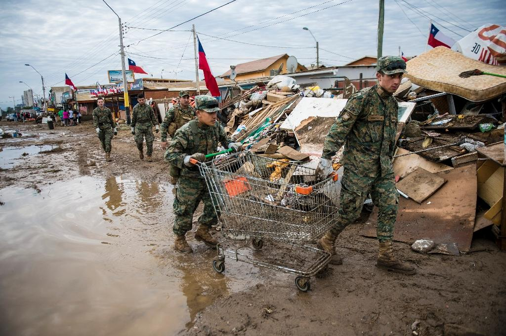 Chilean soldiers clean up the debris left by a tsunami that followed the 8.3 quake in Coquimbo, on September 18, 2015