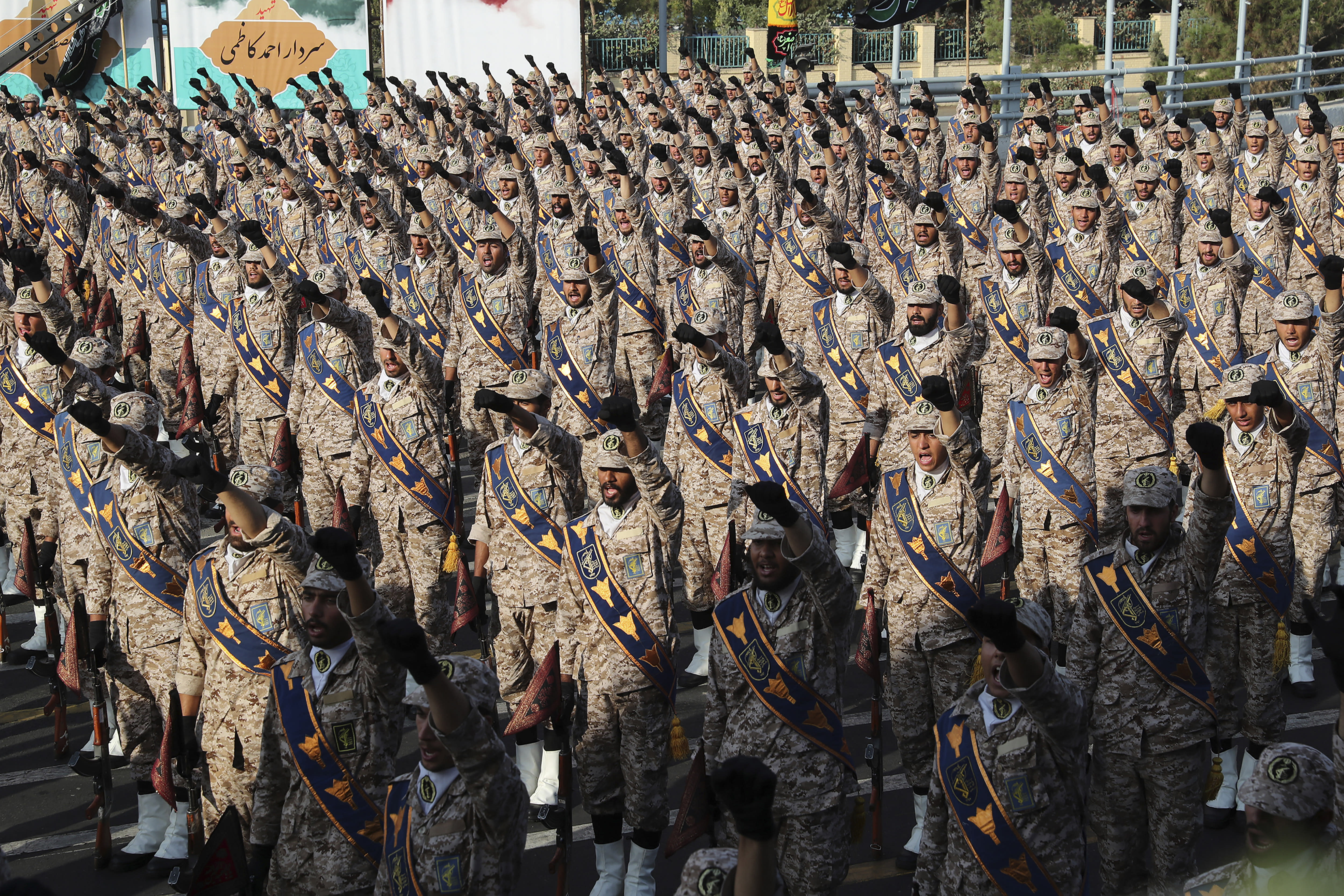In this photo released by the official website of the office of the Iranian Presidency, Revolutionary Guard troops chant slogans at a military parade marking 39th anniversary of outset of Iran-Iraq war, in front of the shrine of the late revolutionary founder Ayatollah Khomeini, just outside Tehran, Iran, Sunday, Sept. 22, 2019. (Iranian Presidency Office via AP)