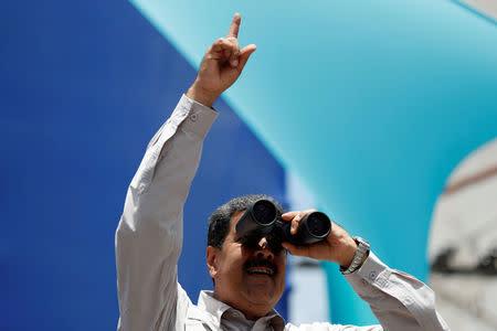 Venezuela's President Nicolas Maduro uses binoculars during a campaign rally in Charallave, Venezuela May 15, 2018. REUTERS/Carlos Garcia Rawlins