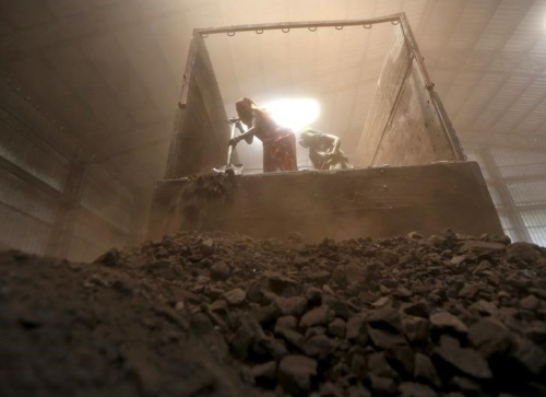 Workers unload coal from supply truck at yard on outskirts of western Indian city of Ahmedabad