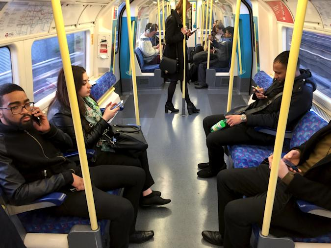 Commuters use their mobile devices on an underground tube train in London April 8, 2015.     REUTERS/Russell Boyce