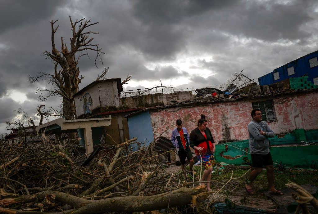 Residents of tornado-hit Regla neighborhood walk amid the debris, in Havana, on January 28, 2019 after a rare and powerful tornado struck (AFP Photo/ADALBERTO ROQUE)