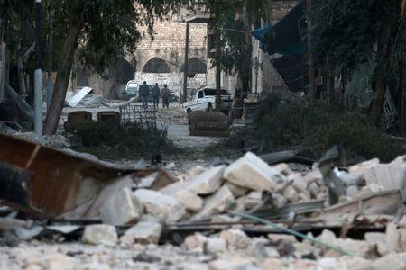 People walk near rubble of damaged buildings, in the rebel-held besieged area of Aleppo