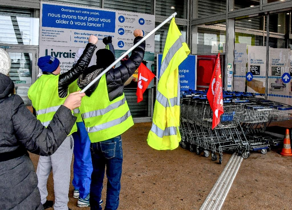"""About 30 """"yellow vest"""" protestors joined striking employees at a hardware store in Englos, northern France, on Friday who were seeking higher pay"""
