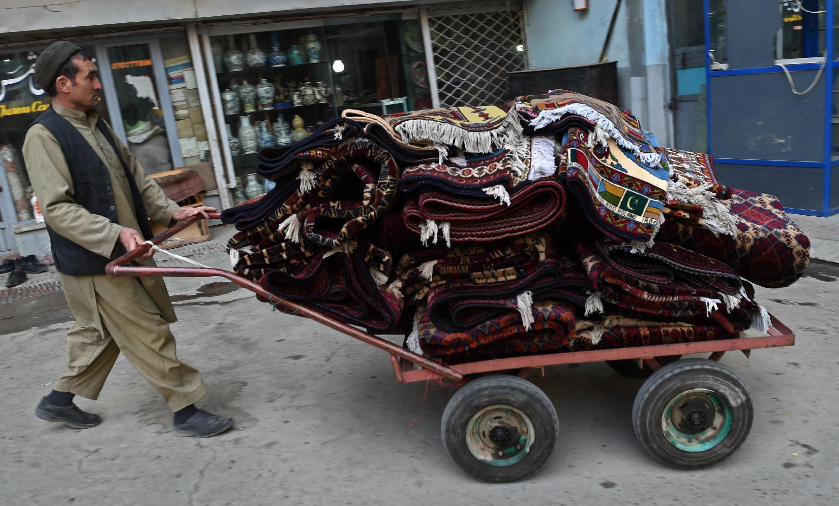 A local worker pushes a cart with carpets along Chicken Street in Kabul, on December 7, 2014 (AFP Photo/Wakil Kohsar)