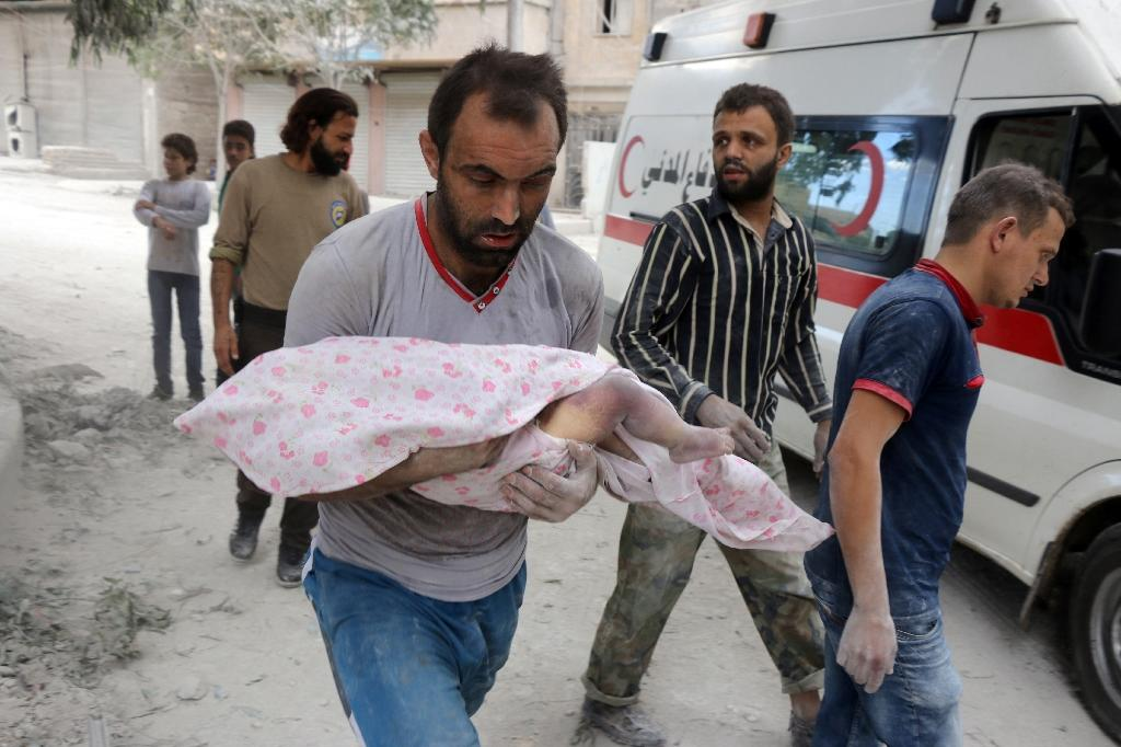 A Syrian man carries the body of an infant retrieved from under the rubble of a building following air raids in Aleppo on September 23, 2016 (AFP Photo/Thaer Mohammed)