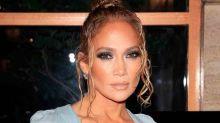 Jennifer Lopez's Bright Orange Pants Melt Into Her Steep Platform Sandals