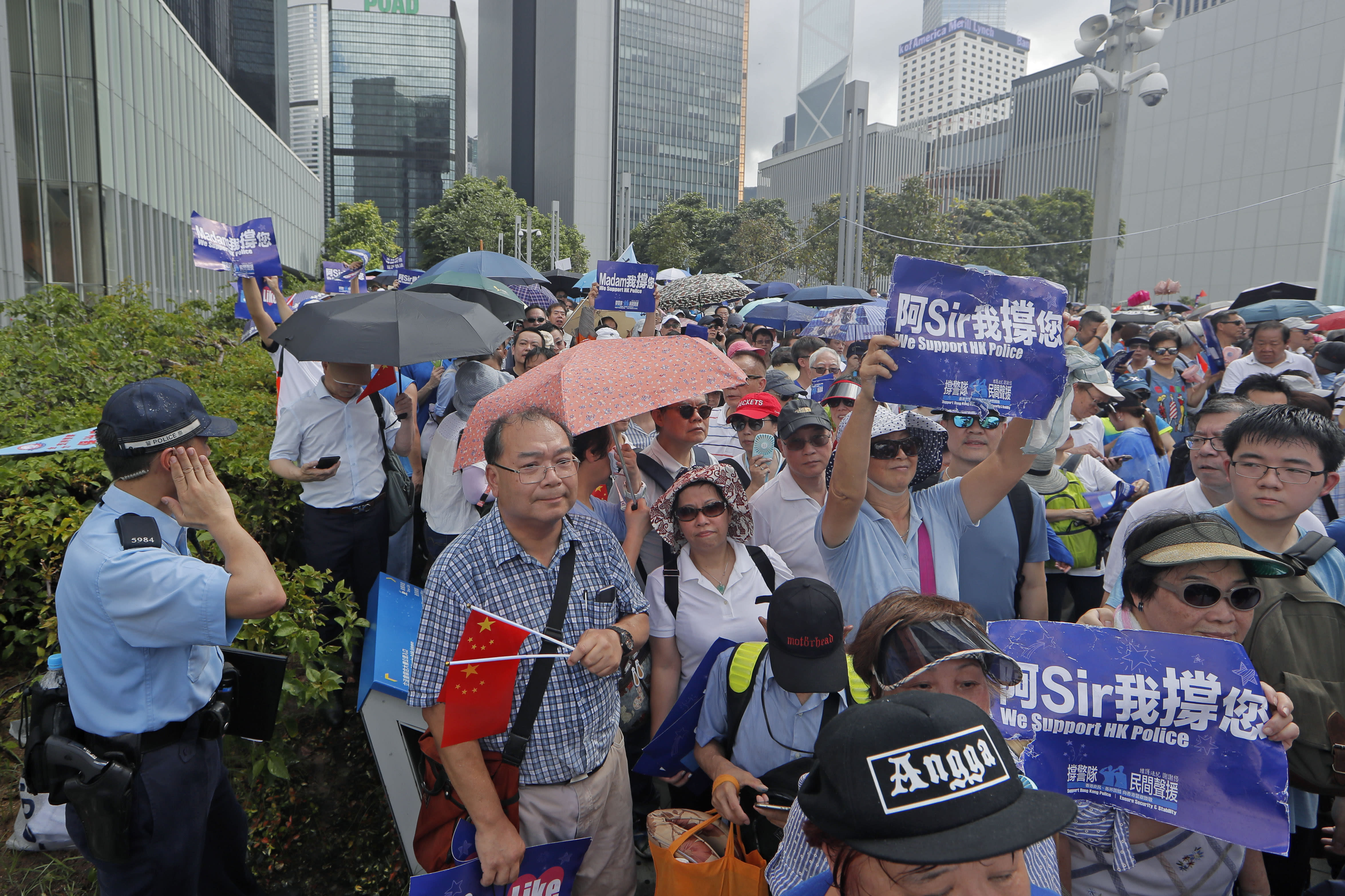 """Pro-China's supporters hold Chinese flags and placards read """"We support HK police"""" during a rally outside Legislative Council Complex in Hong Kong, Sunday, June 30, 2019. Supporters rallied in support of the police at Tamar Park (AP Photo/Kin Cheung)"""