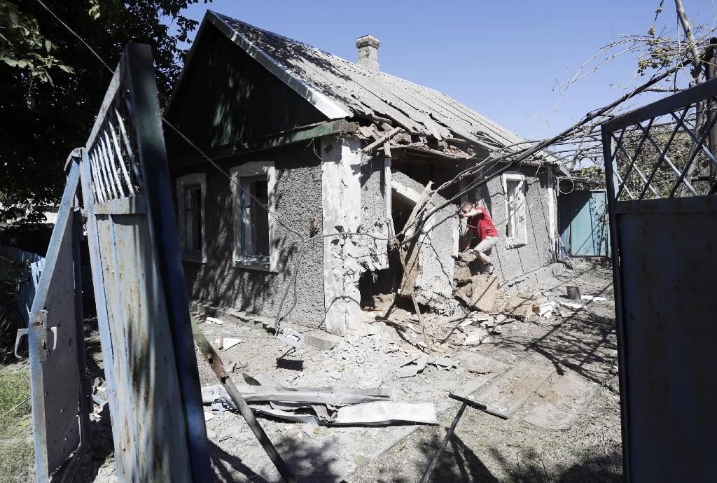A local resident examines his building after it was destroyed by shelling in the small town of Avdiivka, in the Donetsk region of Ukraine, in August 2015 (AFP Photo/Anatolii Stepanov)