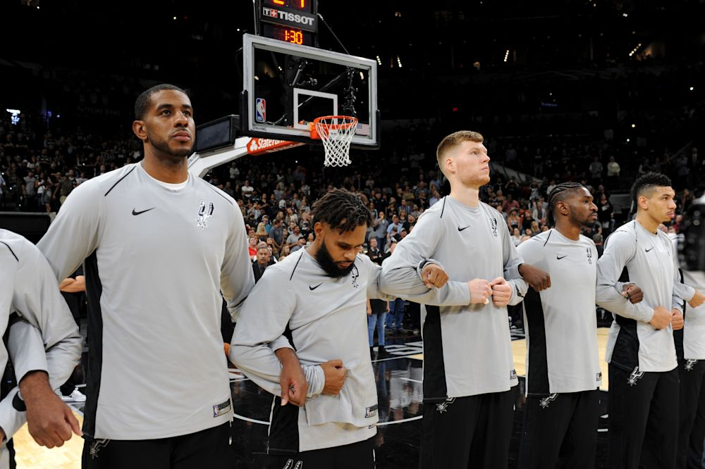 The San Antonio Spurs lock arms after the singing of the National Anthem before their season opener against the Minnesota Timberwolves. (Getty)