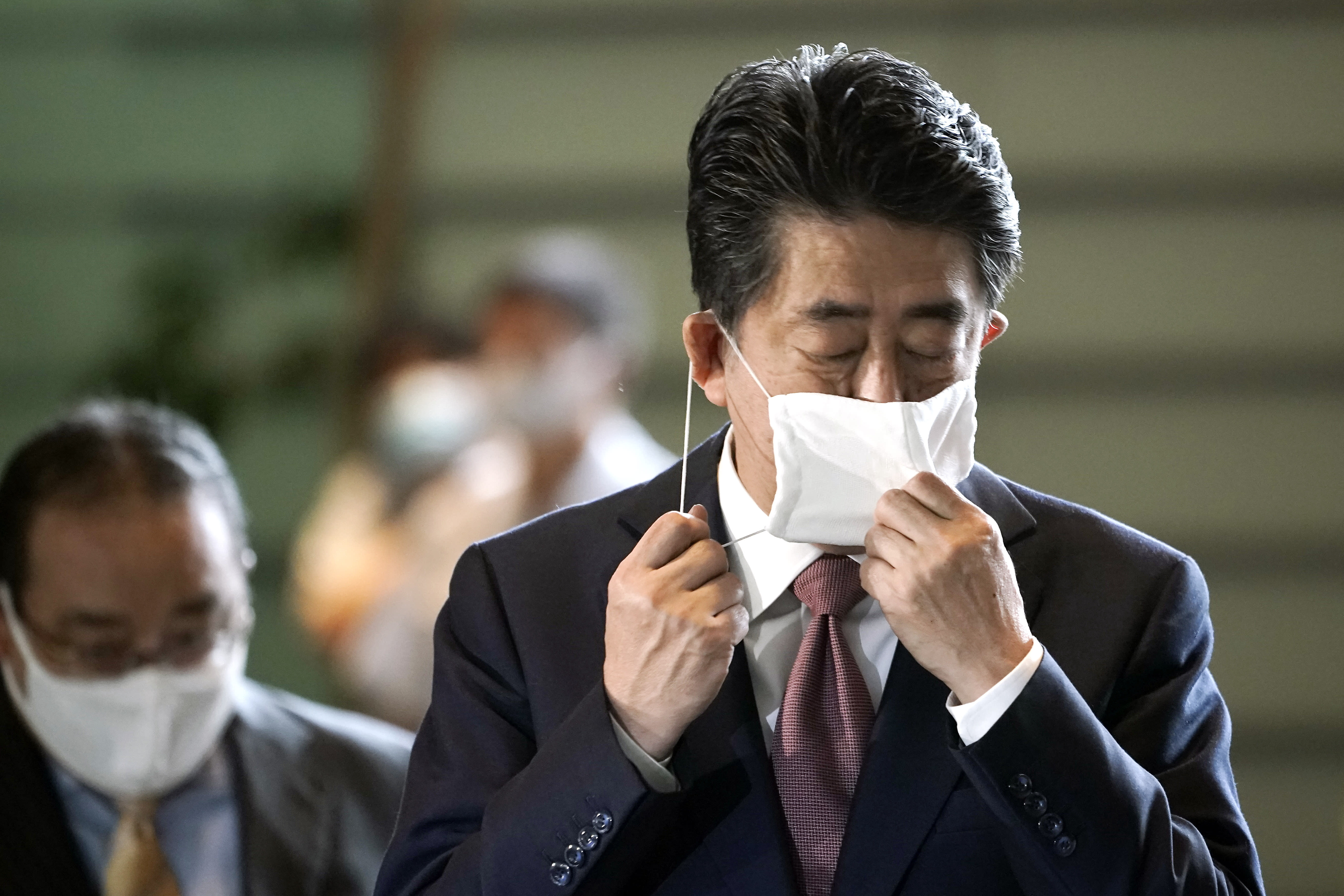 Japan's outgoing Prime Minister Shinzo Abe takes off his face mask as he arrives at the prime minister's office for a cabniet meeting Wednesday, Sept. 16, 2020, in Tokyo. Abe and his Cabinet resigned, clearing the way for his successor Yoshihide Suga to take over after parliamentary confirmation later in the day. (AP Photo/Eugene Hoshiko)