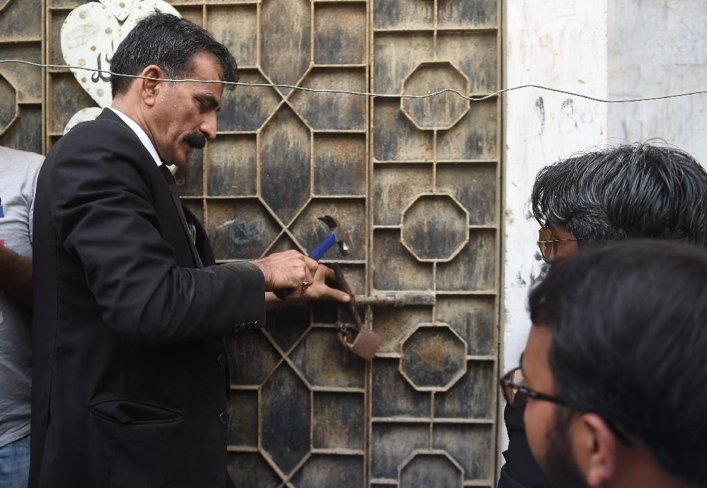 Nawab's lawyer Javed Chatari breaks the lock at her home in Karachi, nearly 20 years after her wrongful arrest (AFP Photo/RIZWAN TABASSUM)