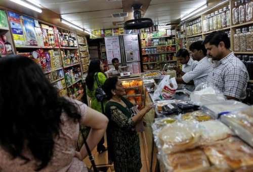 People shop inside a grocery store at a residential area in Mumbai