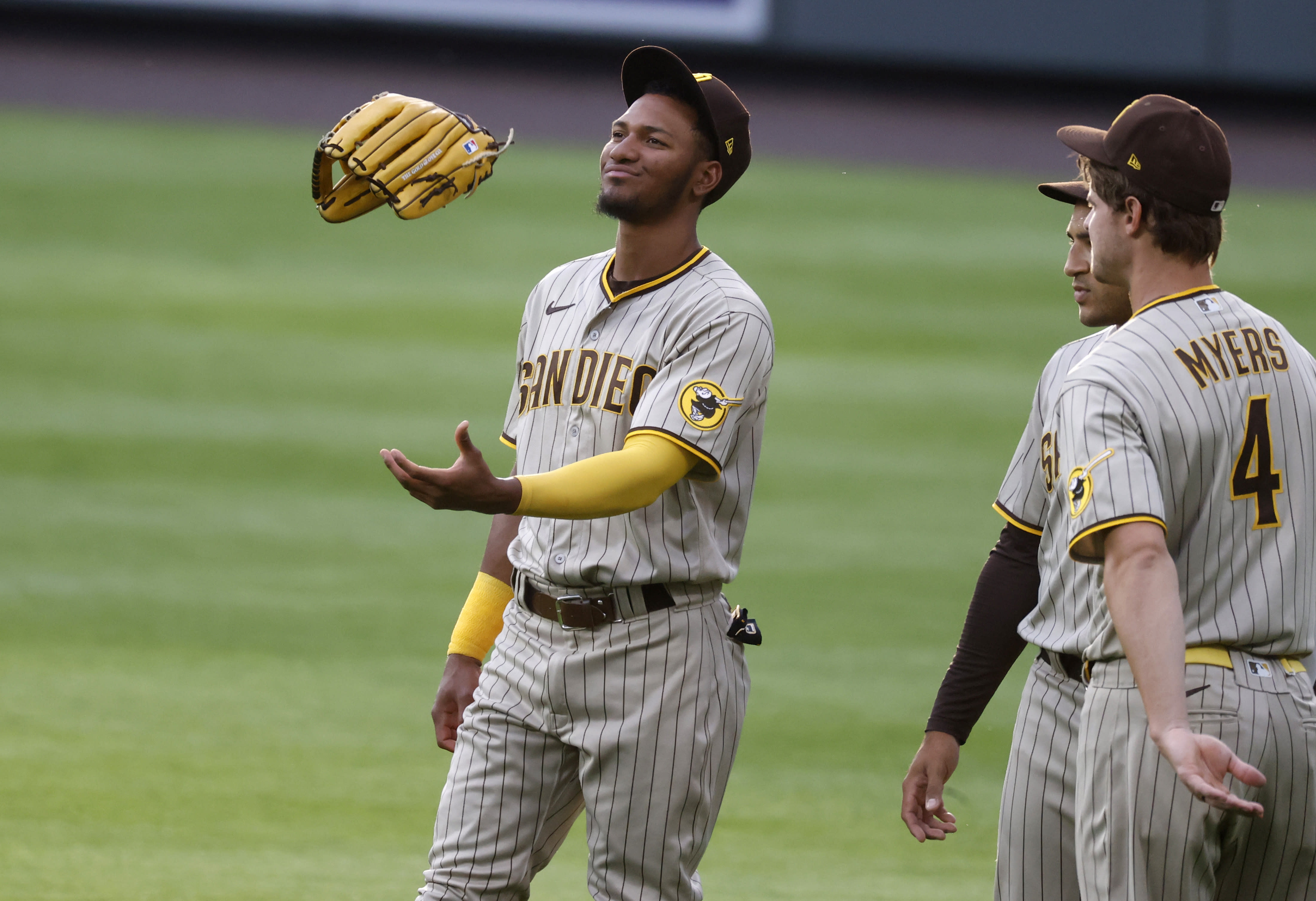 San Diego Padres left fielder Edward Olivares, left, tosses his glove in the air while chatting with center fielder Trent Grisham, center, and San Diego Padres right fielder Wil Myers during a pitching change in the second inning of a baseball game against the Colorado Rockies on Saturday, Aug. 1, 2020, in Denver. (AP Photo/David Zalubowski)