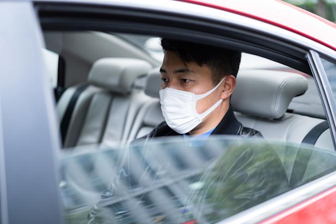 young Asian man with face mask to protect and prevent from the spread of viruses in car