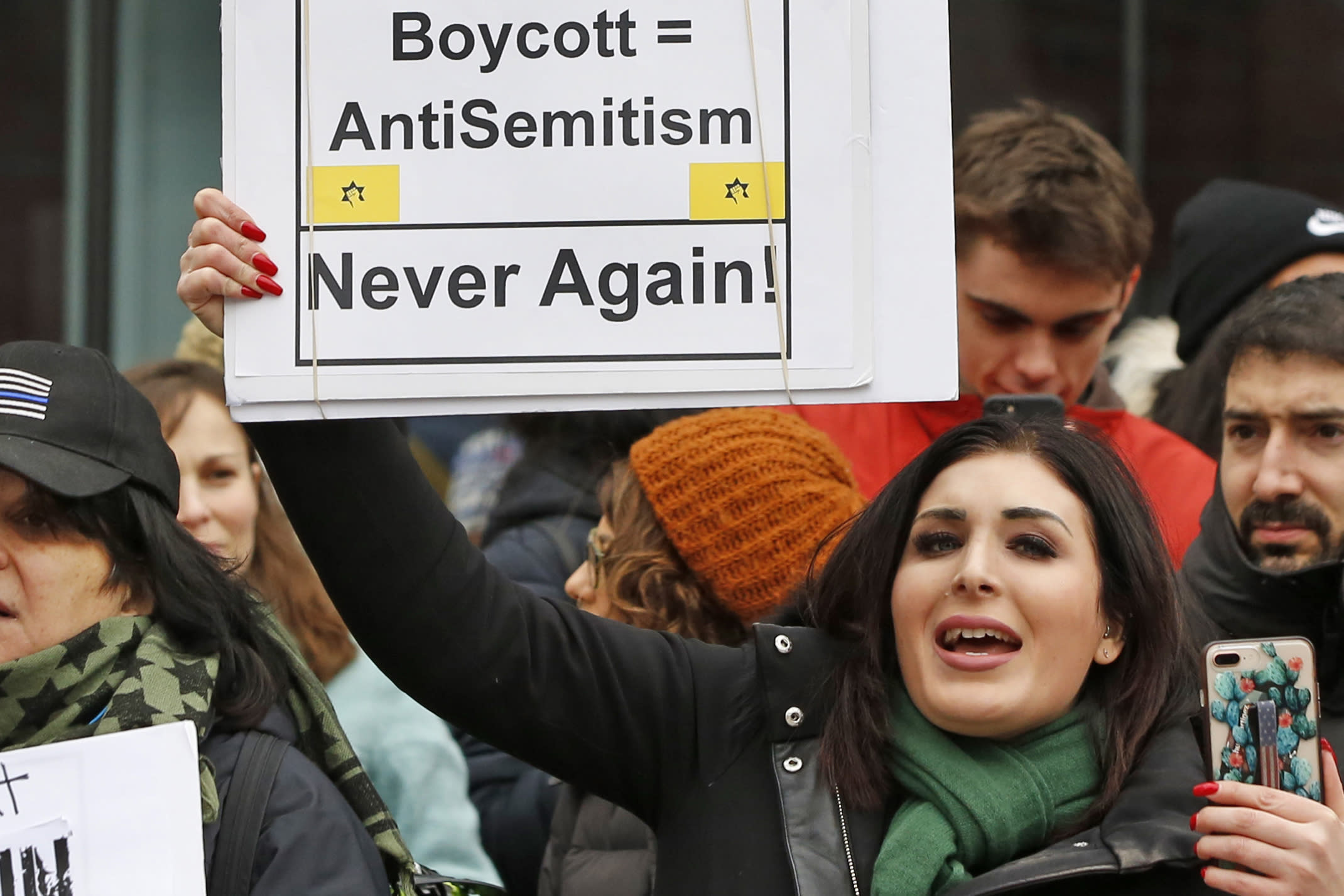 FILE - In this Jan. 19, 2019, file photo, political activist Laura Loomer holds up a sign across the street from a rally organized by Women's March NYC after she barged onto the stage interrupting Women's March NYC director Agunda Okeyo who was speaking during a rally in New York. Loomer, a far-right social media provocateur whose hate speech got her banned from social media won her Republican primary on Tuesday, Aug. 18, 2020, and will challenge Democratic Rep. Lois Frankel for Congress in November. (AP Photo/Kathy Willens, File)