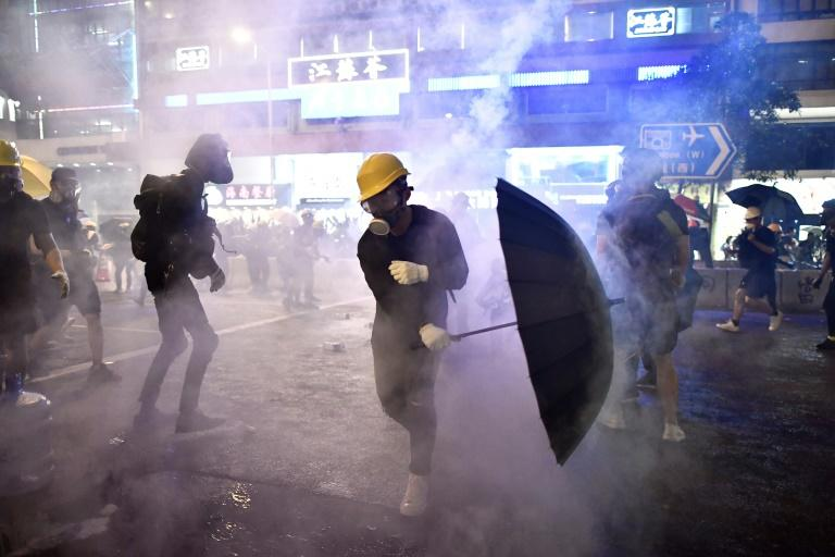 Hong Kong protesters are enveloped by tear gas fired by police (AFP Photo/Anthony WALLACE)