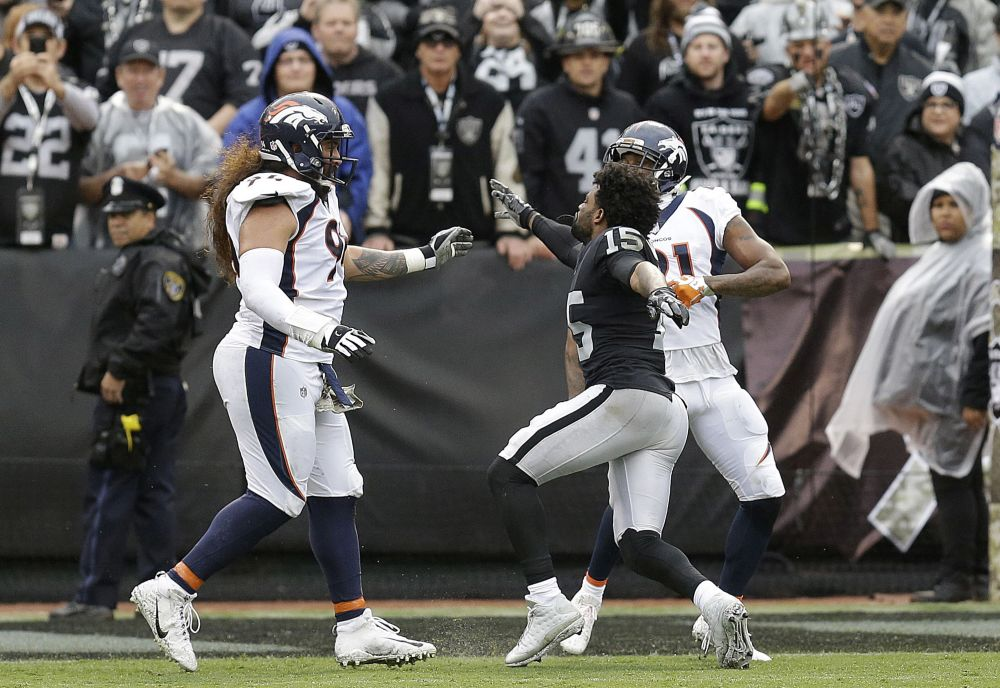 Oakland Raiders wide receiver Michael Crabtree, center, fights with Denver Broncos nose tackle Domata Peko, left, and cornerback Aqib Talib. (AP)