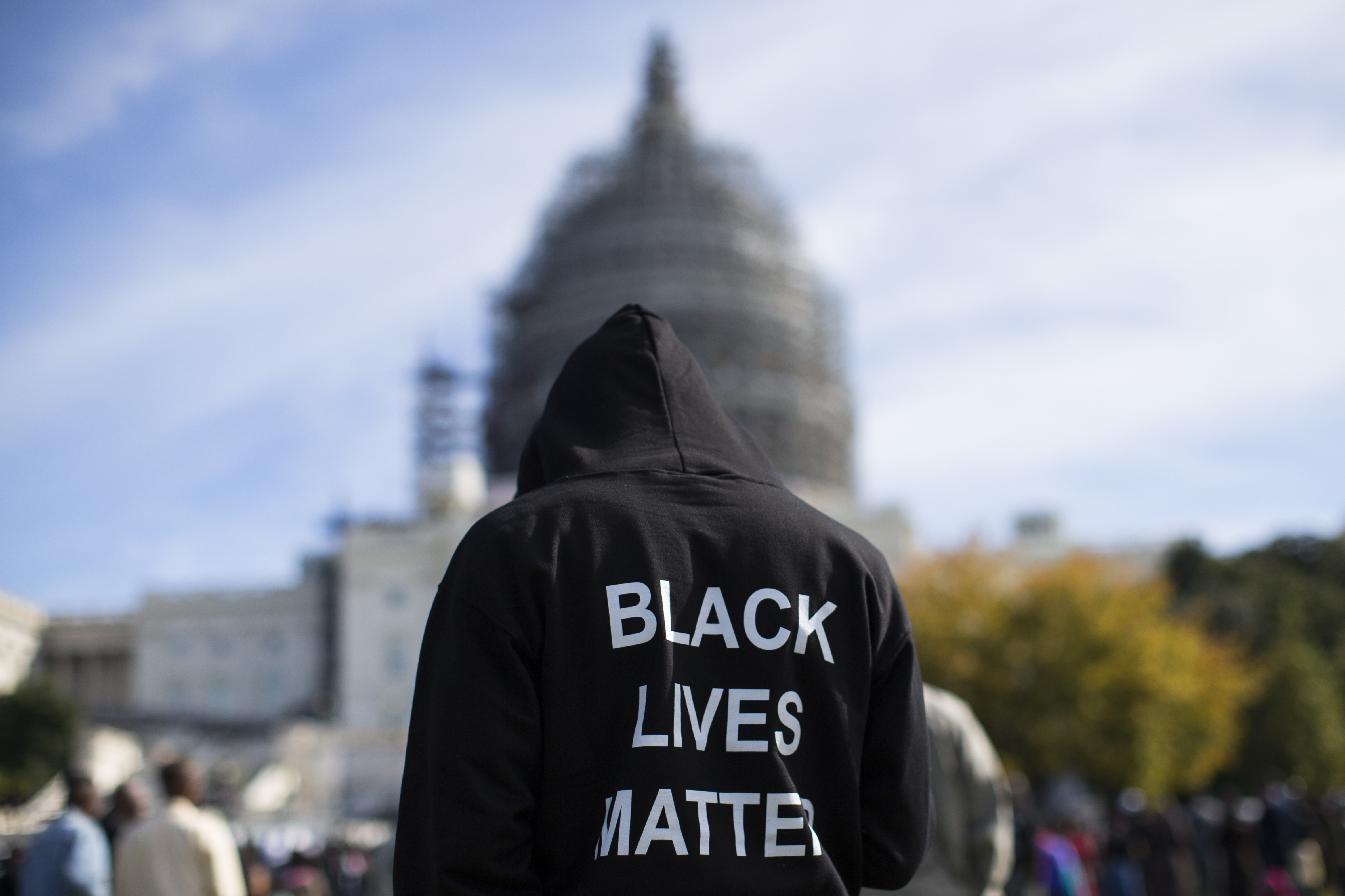 """FILE - In this Oct. 10, 2015 file photo, a man wears a hoodie which reads, """"Black Lives Matter"""" as stands on the lawn of the Capitol building on Capitol Hill in Washington during a rally to mark the 20th anniversary of the Million Man March. Fifty years ago, Martin Luther King Jr. asked Americans, """"Where do we go from here?"""" His warning of chaos or community squarely confronted racism, and marked a shift from his emphasis on nonviolence to a demand for full economic and political equality. Younger generations of black activists say they prefer the pointed, more forceful King to the Nobel Peace Prize-winning pacifist who preached love over hate. (AP Photo/Evan Vucci, File)"""