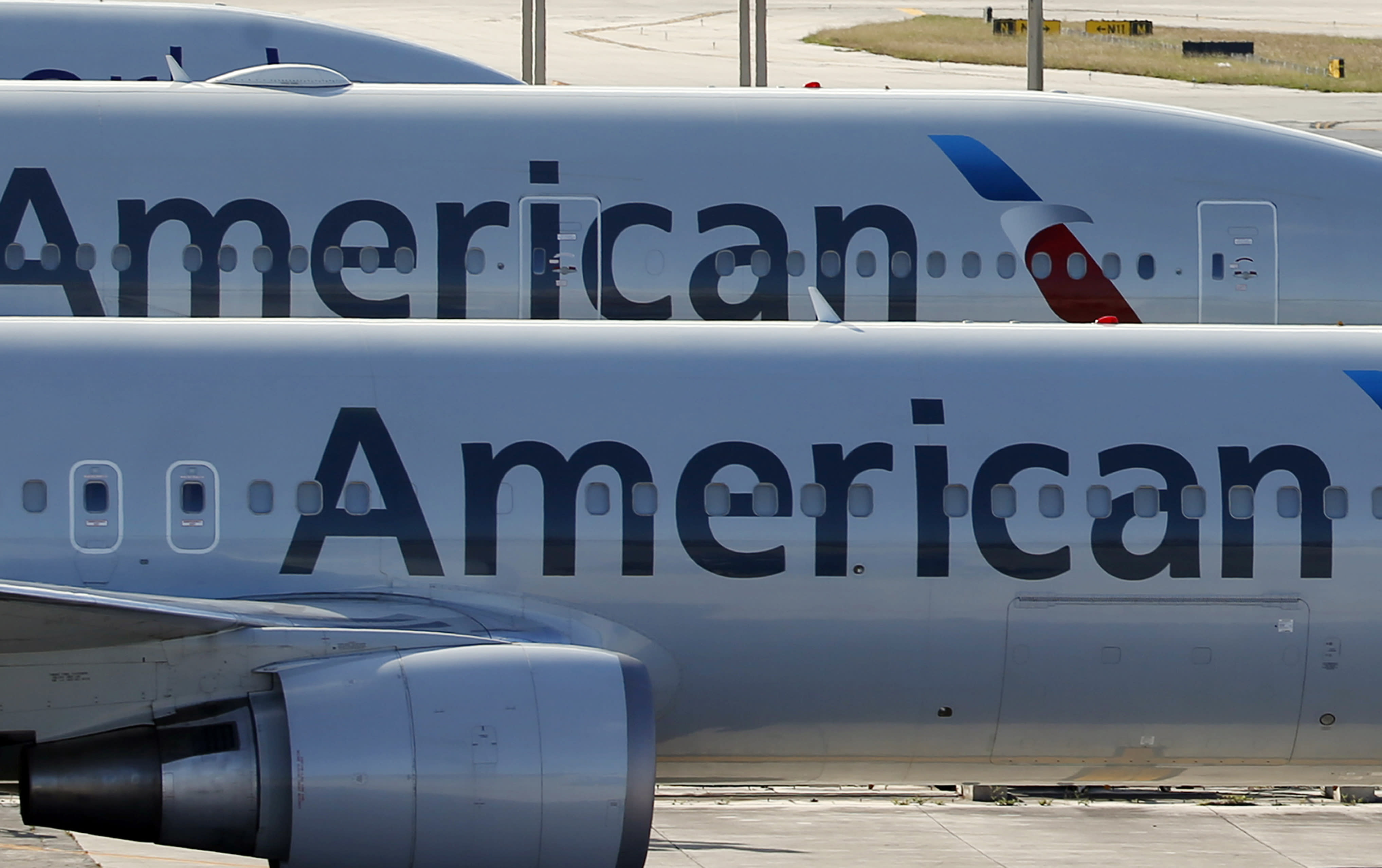 """FILE - In this Nov. 6, 2017, file photo, a pair of American Airlines jets are parked on the airport apron at Miami International Airport in Miami. American Airlines is threatening to prohibit customers from making changes to nonrefundable tickets if Congress makes good on a proposal to crack down on unreasonable airline fees. American CEO Doug Parker says his airline would be acting just like many other businesses when customers want to swap their ticket for a different flight or for another day. """"We - like the baseball team, like the opera - would say, 'We're sorry, it was nonrefundable,'"""" Parker said this week. (AP Photo/Wilfredo Lee, File)"""
