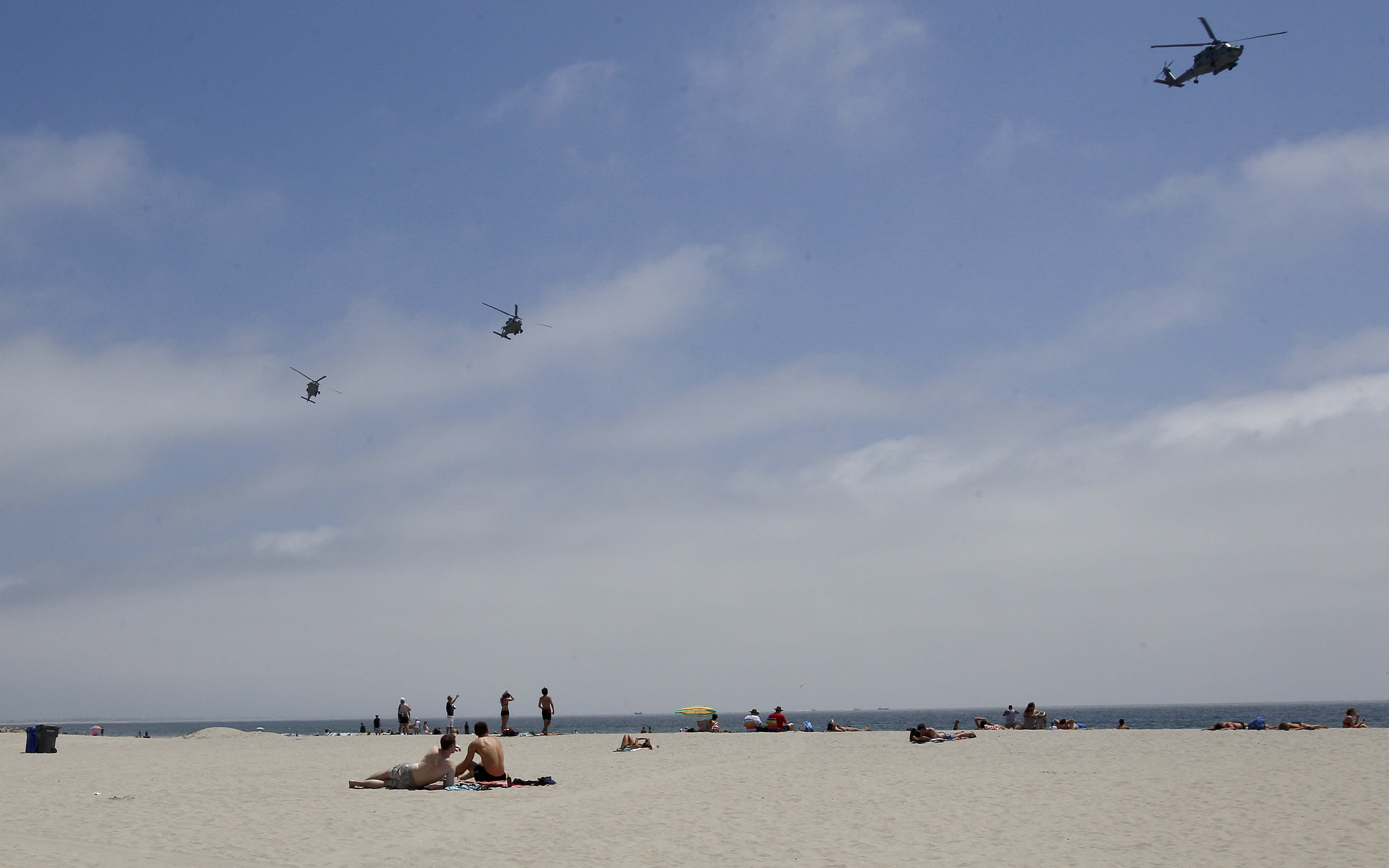 "In this May 22, 2012 photo, part of a Navy helicopter squadron flies over beach goers on the Coronado Beach in Coronado, Calif. The Coronado Beach has been named America's best beach. Coronado Beach tops the 2012 list of Top 10 Beaches produced annually by coastal expert Stephen P. Leatherman, also known as ""Dr. Beach,"" director of Florida International University's Laboratory for Coastal Research. (AP Photo/Lenny Ignelzi)"
