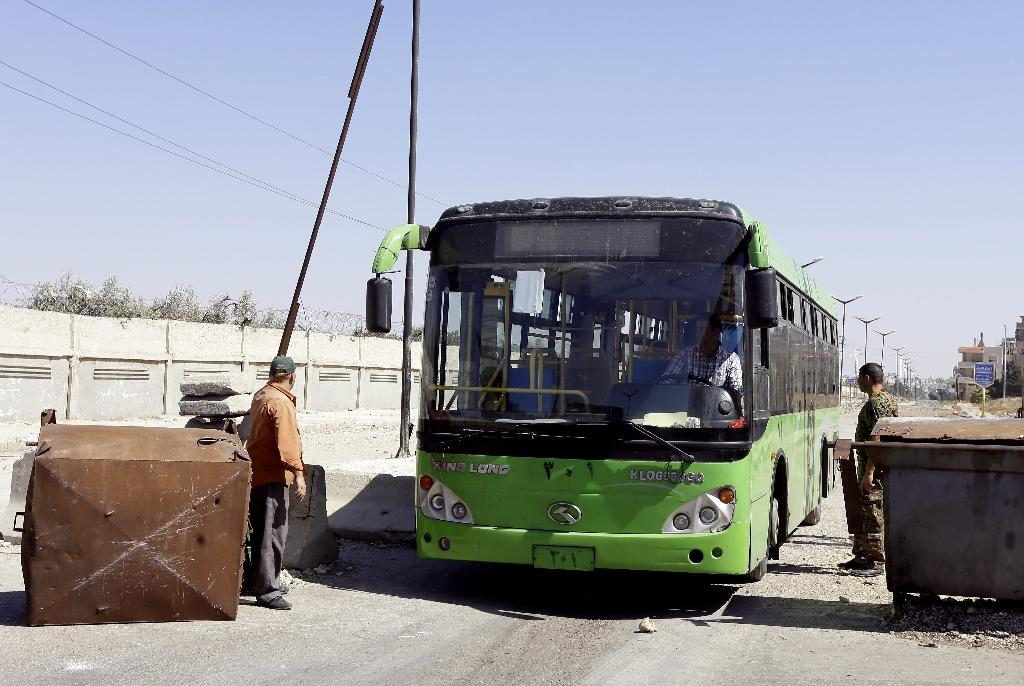A Syrian soldier lets an empty bus pass through a checkpoint on the frontier of the rebel-held al-Waer neighbourhood in the central Syrian city of Homs on September 19, 2016 (AFP Photo/Louai Beshara)