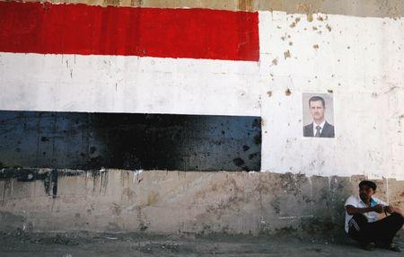 FILE PHOTO: A man sits near a poster of Syrian President Bashar al-Assad during the re-opening of the road between Homs and Hama in Talbisi, Syria June 6, 2018. REUTERS/Omar Sanadiki/File Photo