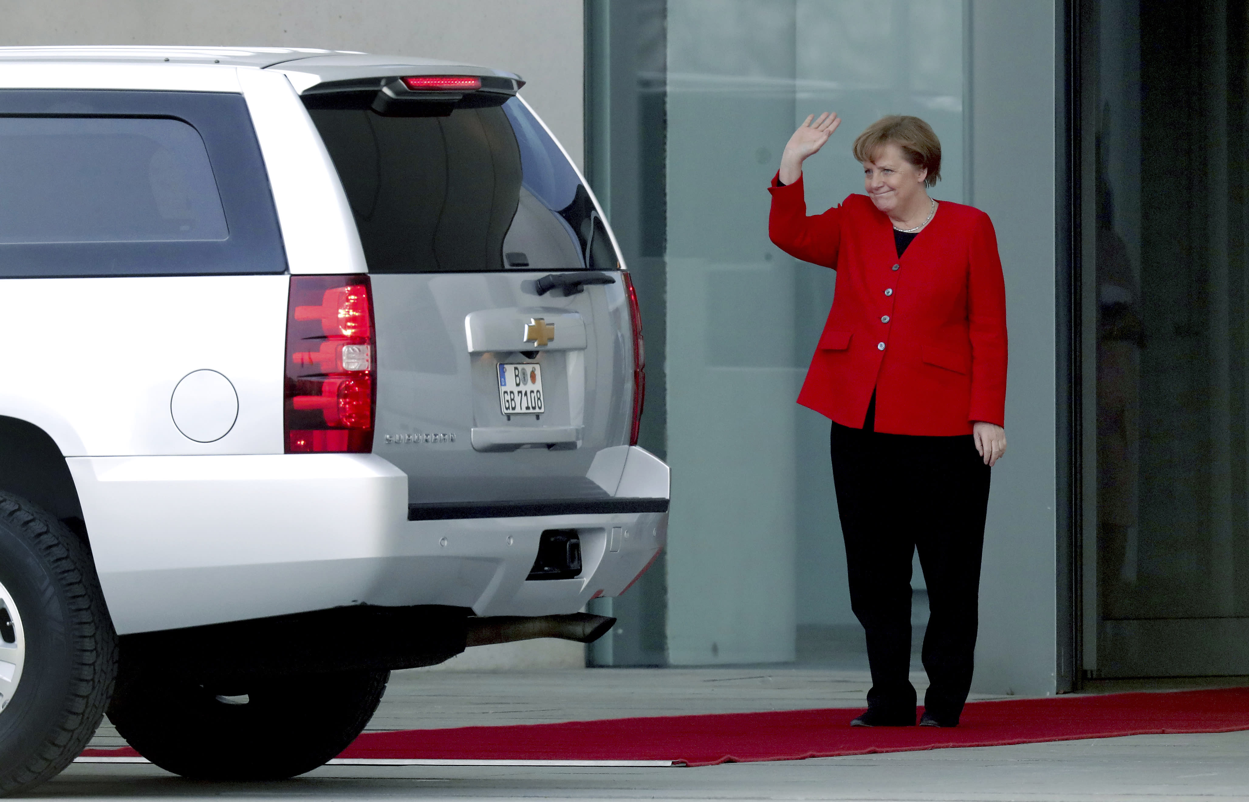 German Chancellor Angela Merkel waves farewell to former US President Barack Obama after a meeting at the chancellery in Berlin, Germany, Friday, April 5, 2019. (AP Photo/Michael Sohn)