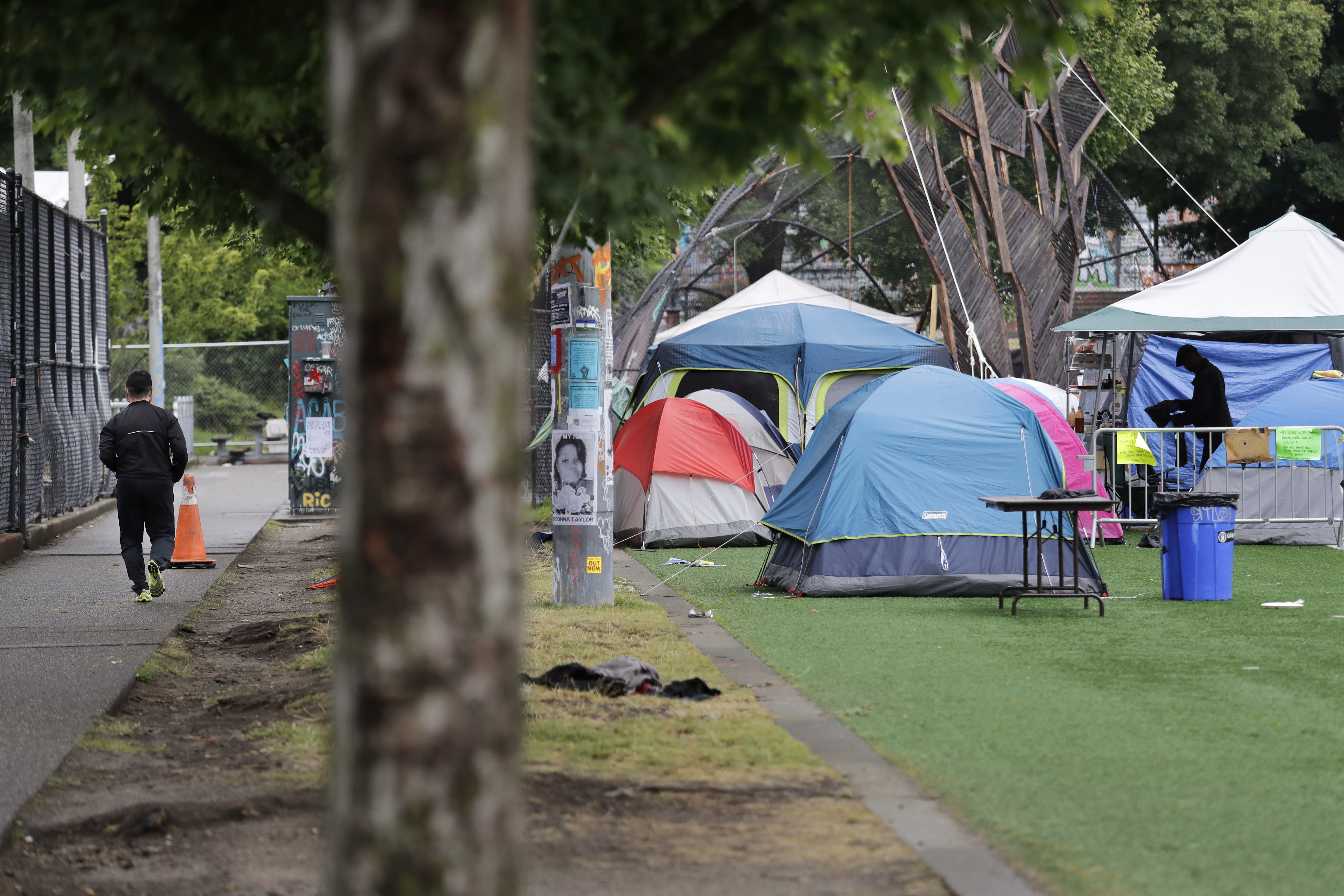 A jogger, left, runs past tents set-up on a play field in a city park Sunday, June 28, 2020, in Seattle, where several streets are blocked off in what has been named the Capitol Hill Occupied Protest zone. Seattle Mayor Jenny Durkan met with demonstrators Friday after some lay in the street or sat on barricades to thwart the city's effort to dismantle the protest zone that has drawn scorn from President Donald Trump and a lawsuit from nearby businesses. (AP Photo/Elaine Thompson)