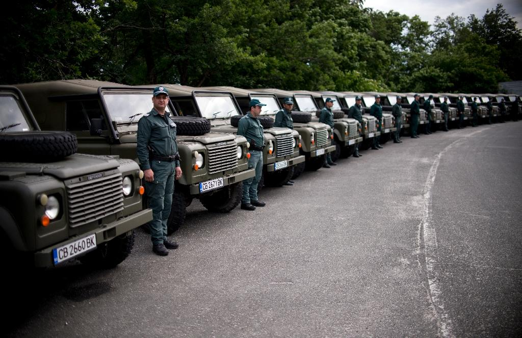 Bulgarian border police personal stand between military vehicles donated to Bulgarian government by the United Kingdom at the border between Bulgaria and Turkey on May 22, 2016