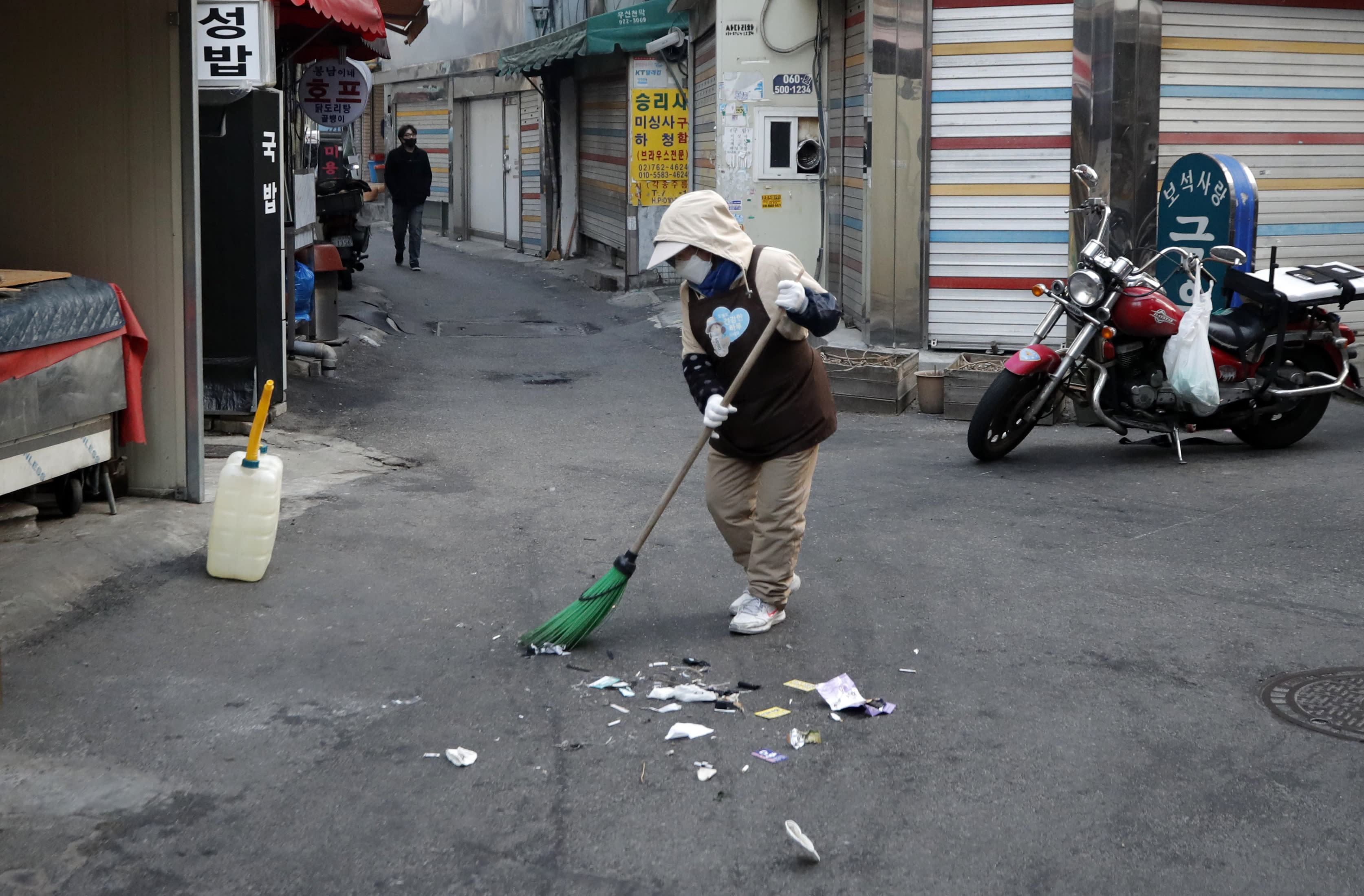 A woman wearing a face mask sweeps on the street in the morning in Seoul, South Korea, Wednesday, March 18, 2020. For most people, the new coronavirus causes only mild or moderate symptoms. For some it can cause more severe illness. (AP Photo/Lee Jin-man)
