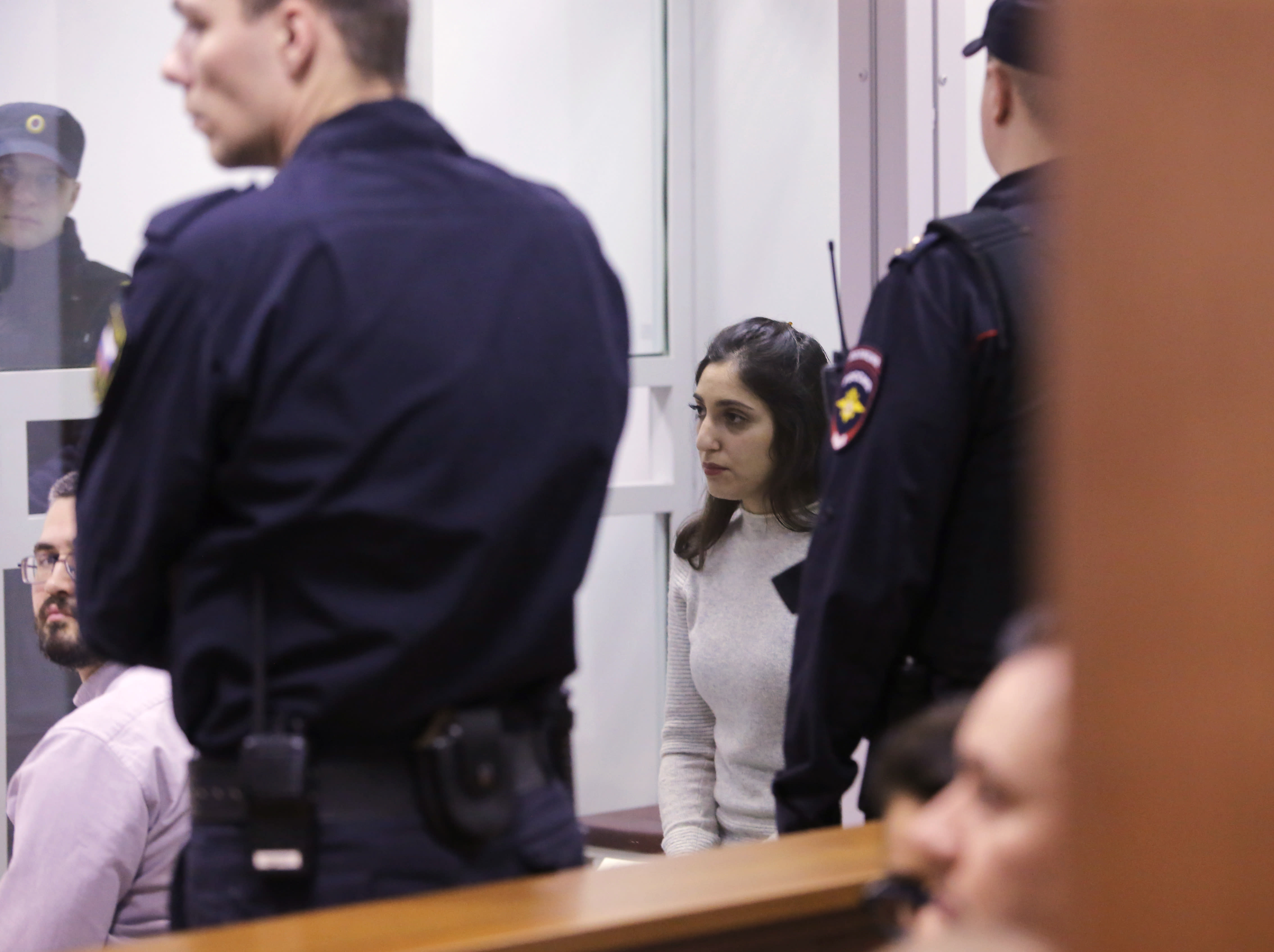 Israeli woman Naama Issachar, centre, sits inside a cage during appeal hearings in a courtroom in Moscow, Russia, Thursday, Dec. 19, 2019. Naama was sentenced in October to seven and a half years in prison for drug smuggling after authorities in April found nine grams of marijuana in her luggage. (AP Photo/Alexander Zemlianichenko Jr.)