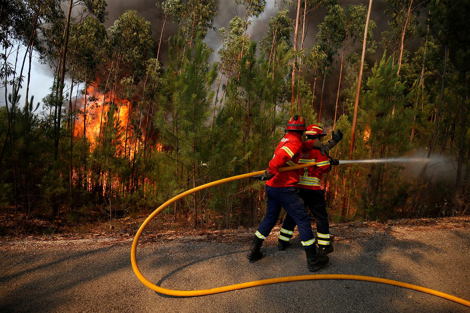 <p>Firefighters work to put out a forest fire next to the village of Macao, near Castelo Branco, Portugal, July 26, 2017. (Rafael Marchante/Reuters) </p>