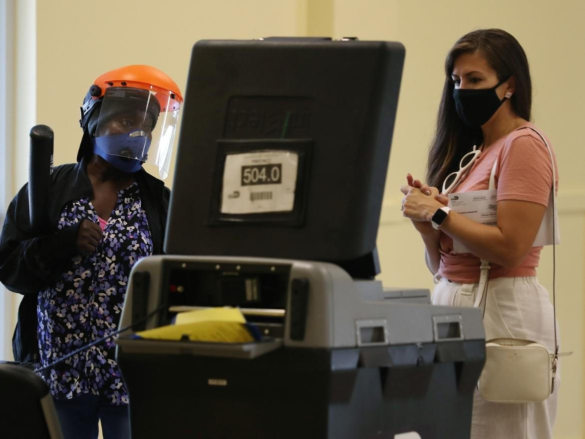 A poll worker looks on as Maria Bilbao casts her vote on primary election day in Miami.