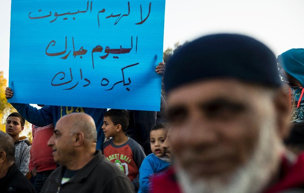 """Israeli Arabs hold a poster reading in Arabic """"No to the demolition of houses, today it is your neighbour, tomorrow it will be you"""" the day after the demolition of houses over building permits in the Israeli Arab city of Qalansuwa on January 11, 2017 (AFP Photo/JACK GUEZ)"""