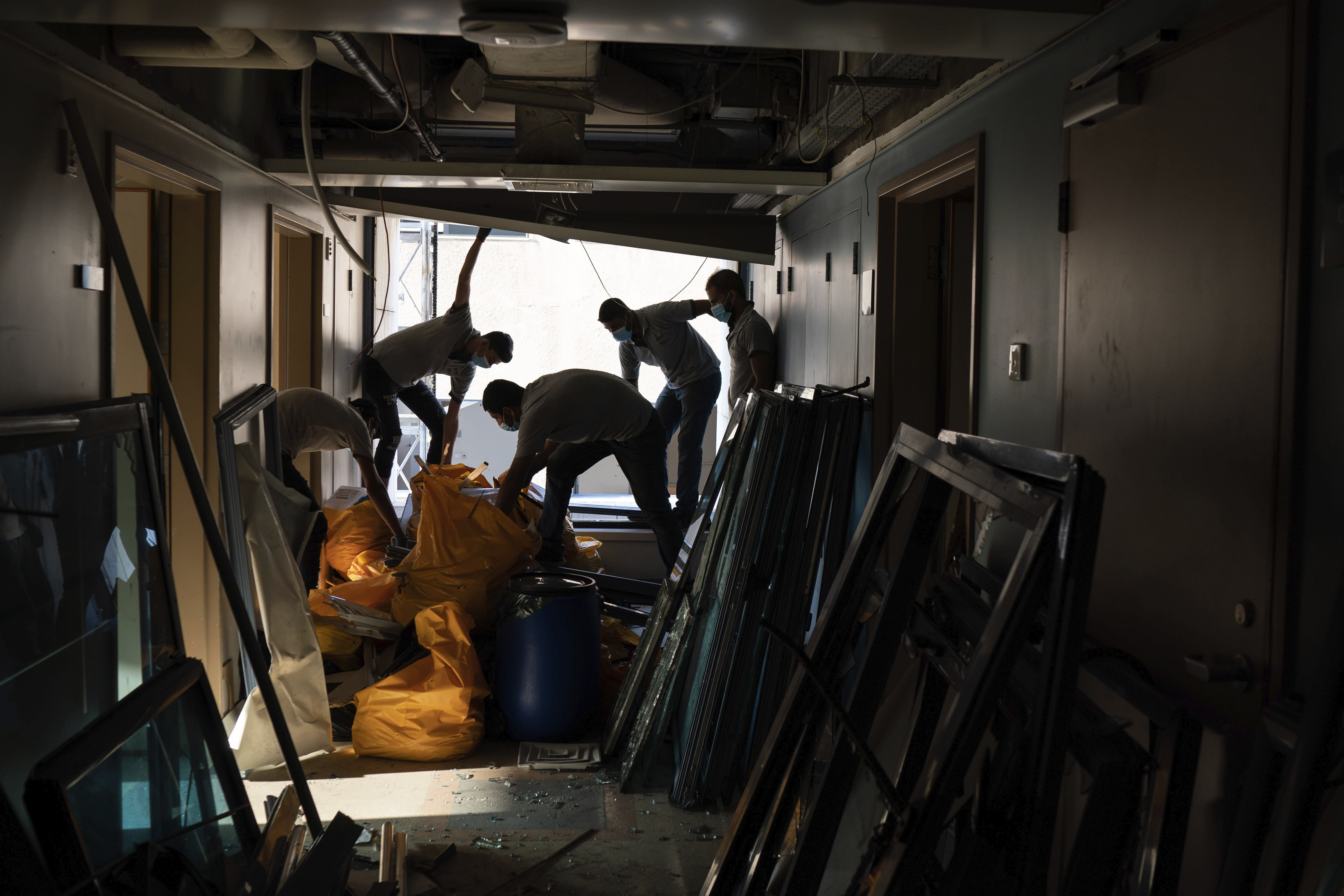 FILE - In this August 13, 2020 file photo, workers remove debris from the Saint George Hospital, that was heavily damaged in the Aug. 4 massive explosion in Beirut, Lebanon. Lebanon's health services and facilities were once considered among the region's best. But in a short time, they have been brought to near collapse, battered by Lebanon's financial meltdown and a surge in coronavirus cases, then smashed by the Beirut explosion. (AP Photo/Felipe Dana, File)