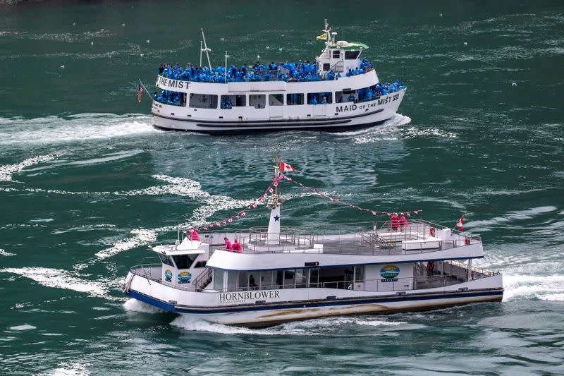 American tourist boat glides past a Canadian vessel limited to just six passengers in Niagara Falls