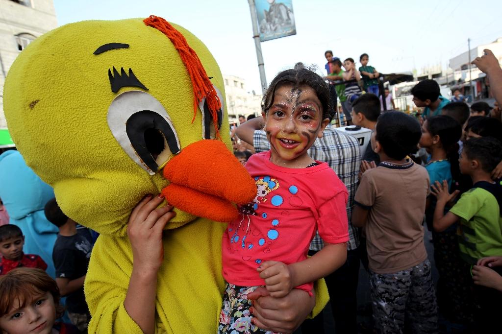 A Palestinian wearing a duck mask carries a girl during a street celebration ahead of the beginning of the Muslim holy month of Ramadan in Gaza City on June 5, 2016 (AFP Photo/Said Khatib)