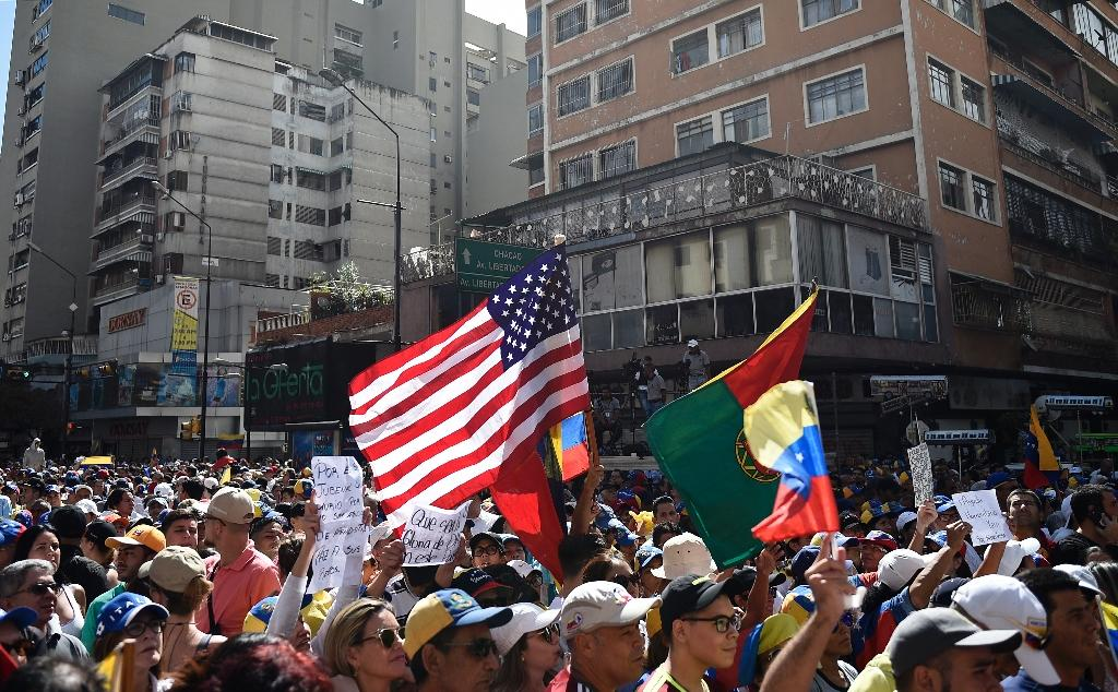 A US flag is seen amid the crowd of supporters of Venezuelan opposition leader Juan Guaido, as people start gathering for a rally to press the military to let in US humanitarian aid, in Caracas on February 12, 2019 (AFP Photo/Federico PARRA)